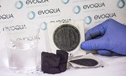 Evoqua lab tech holding test paper with dry cake and water